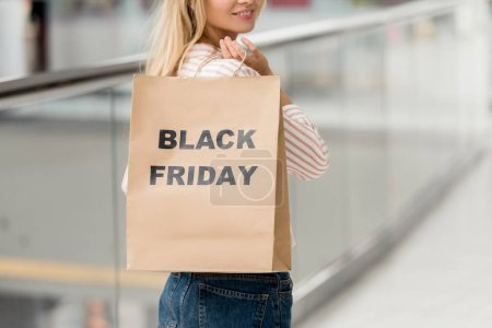 partial view of woman holding paper bag with lettering black friday at shopping mall
