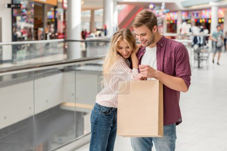 couple of shoppers looking down and holding paper bag at shopping mall