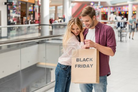 young couple of shoppers looking down and holding paper bag with lettering black friday at shopping mall