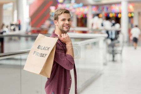 young smiling man holding paper with lettering black friday and looking at camera at shopping mall