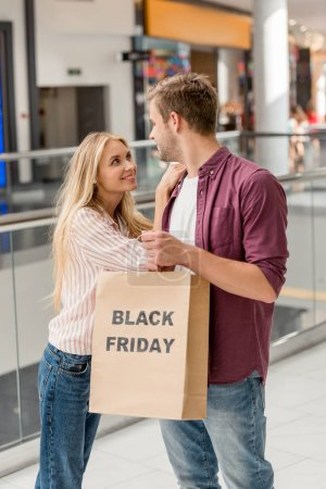 smiling young couple of shoppers holding paper bag with lettering black friday at shopping mall