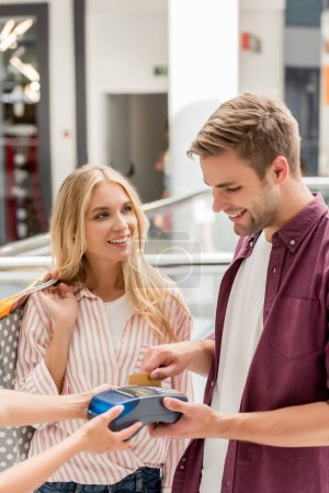 smiling man paying by credit card on terminal while his girlfriend standing near with shopping bags at mall