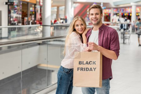 happy young couple of shoppers holding paper bag with lettering black friday at shopping mall
