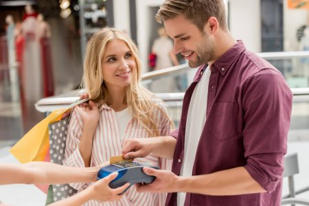 young man paying by credit card on terminal while his girlfriend standing near with shopping bags at mall