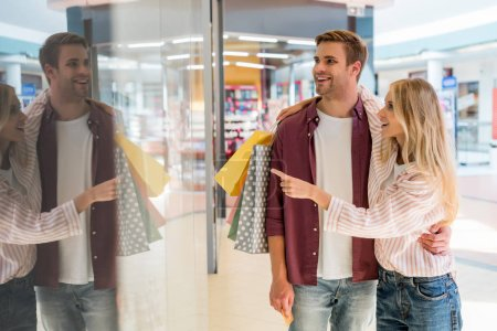 young woman with shopping bags pointing by finger at shopwindow to boyfriend at mall