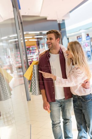 Photo for Smiling young woman with shopping bags pointing by finger at shopwindow to boyfriend at mall - Royalty Free Image