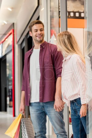 Photo for Happy young couple with paper bags walking out from store at shopping mall - Royalty Free Image