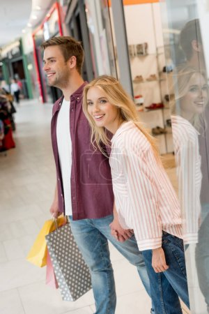 Photo for Couple of shoppers with paper bags walking out from store at shopping mall - Royalty Free Image