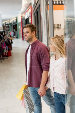 Photo for Smiling young couple with paper bags walking out from store at shopping mall - Royalty Free Image