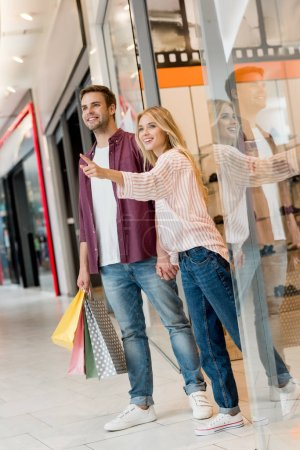 happy young woman pointing by finger to boyfriend with shopping bags at mall
