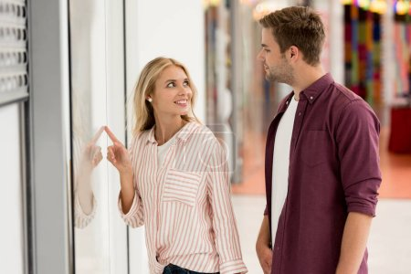 young woman pointing by finger at shopwindow to boyfriend with shopping bags at mall