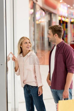 smiling woman pointing by finger at shopwindow to boyfriend with shopping bags at mall