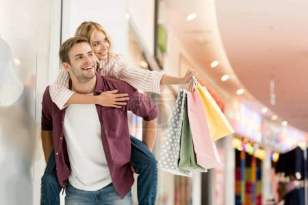 Photo for Happy young man giving piggyback ride to girlfriend with shopping bags at mall - Royalty Free Image