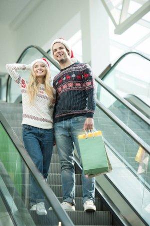 Foto de Vista de ángulo bajo de par de los compradores en sombreros de la Navidad con bolsas de papel en escalera mecánica - Imagen libre de derechos