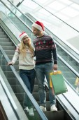 happy young couple of shoppers in christmas hats holding papers bags on escalator