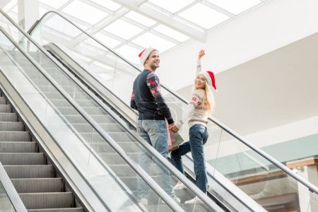 Photo for Young woman in christmas hat with raised arms looking at camera while her boyfriend standing near on escalator - Royalty Free Image