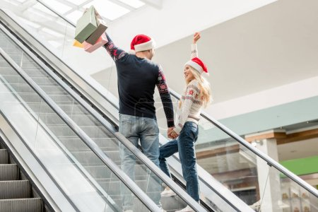 rear view of couple of shoppers in christmas hats with raised arms holding papers bags on escalator