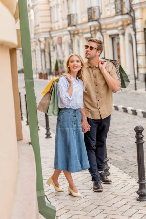 young stylish couple with shopping bags walking at urban street