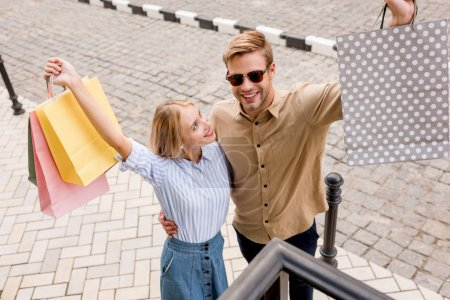 high angle view of excited couple with raised arms holding shopping bags at city street