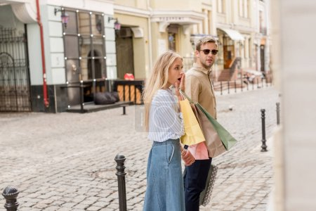 shocked young woman with shopping bags closing mouth by hand while her boyfriend standing near shopwindows on street