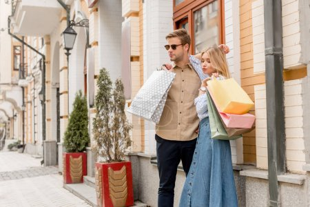 Photo for Young couple of shoppers with paper bags posing at urban street - Royalty Free Image