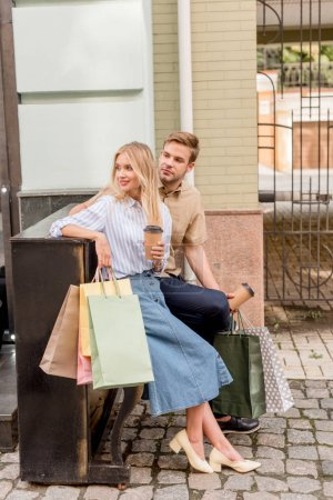 stylish couple with shopping bags and paper cups of coffee standing near piano at urban street