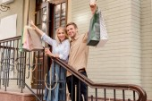 happy young couple with coffee cups showing shopping bags and standing on staircase at city street