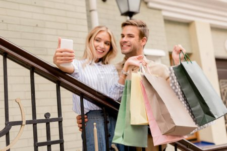 smiling young couple with paper bags taking selfie on smartphone near store at city street