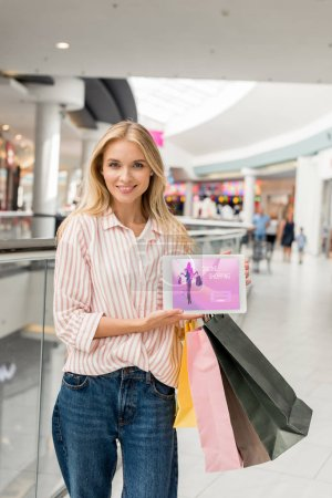 smiling young woman with paper bags showing digital tablet with online shopping on screen at mall