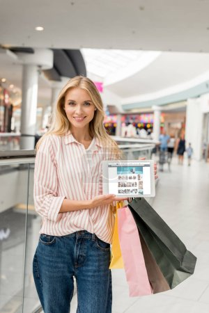 attractive woman with shopping bags showing digital tablet with amazon website on screen at mall