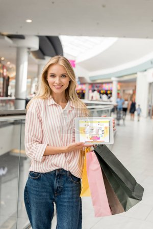 young woman with shopping bags showing digital tablet with aliexpress website on screen at mall
