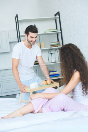 happy young man holding tray with breakfast and looking at girlfriend in bedroom
