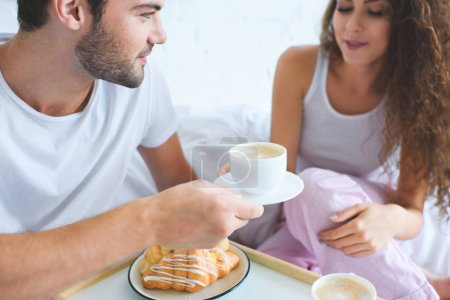 Photo for Cropped shot of young couple having croissants and coffee for breakfast in bed - Royalty Free Image