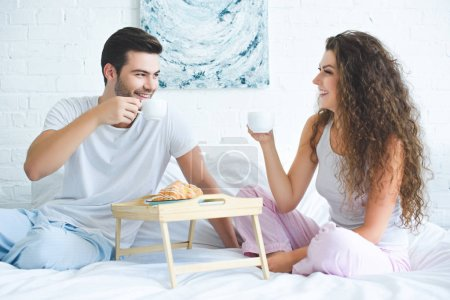 happy young couple in pajamas drinking coffee and smiling each other while sitting on bed