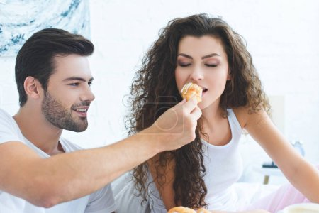 smiling young man feeding beautiful girlfriend with croissant for breakfast in bedroom