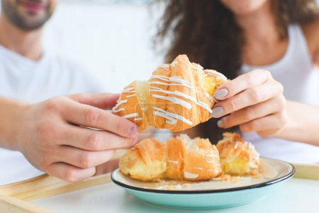 close-up view of young couple sharing croissant for breakfast