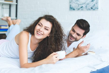 happy young couple holding cups of coffee and laughing on bed