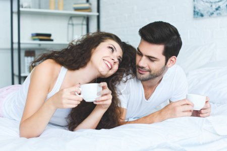 beautiful happy young couple holding cups of coffee and lying on bed
