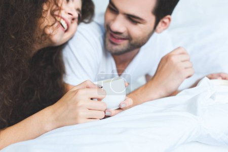 cropped shot of happy young couple holding cups of coffee and lying on bed