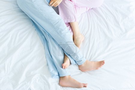 low section of young couple in pajamas lying together on bed