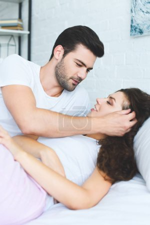 beautiful happy young couple in love smiling each other while lying together in bed