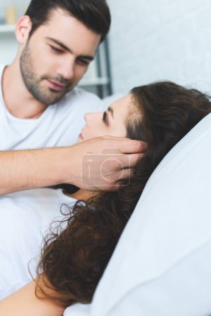 beautiful young couple in love looking at each other while lying together in bed