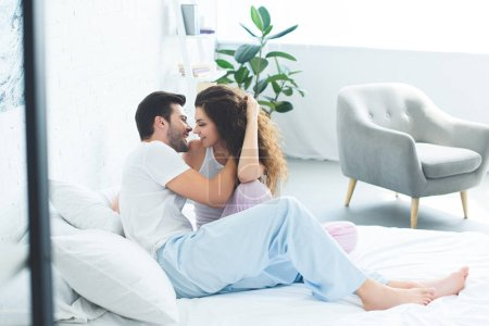 beautiful happy young couple in pajamas kissing on bed