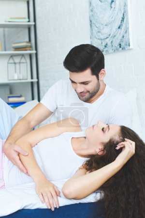 handsome smiling young man looking at beautiful girlfriend sleeping on bed