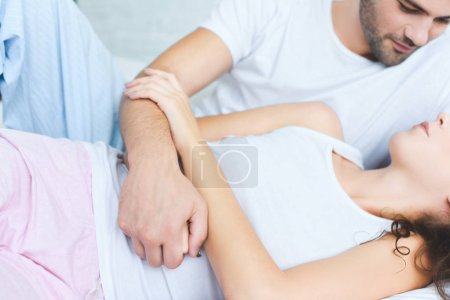 cropped shot of man in pajamas looking at girlfriend lying on bed
