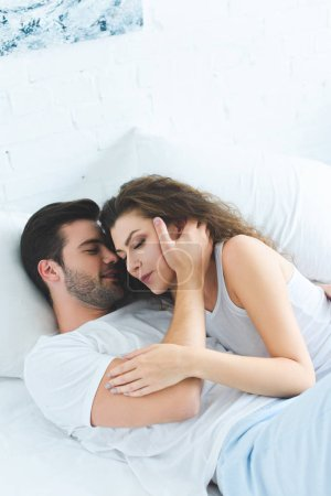 high angle view of beautiful young couple in love lying together in bed