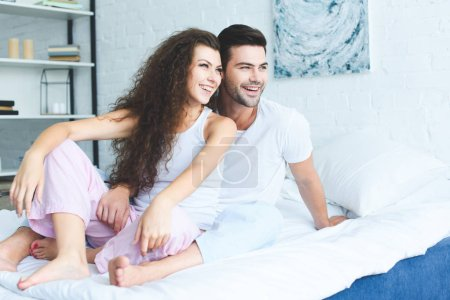 Photo for Happy young couple in pajamas sitting together on bed and looking away - Royalty Free Image