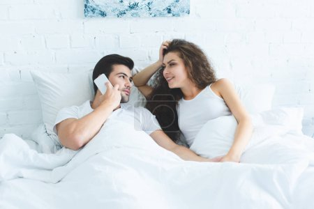 high angle view of smiling young woman looking at boyfriend talking by smartphone in bed