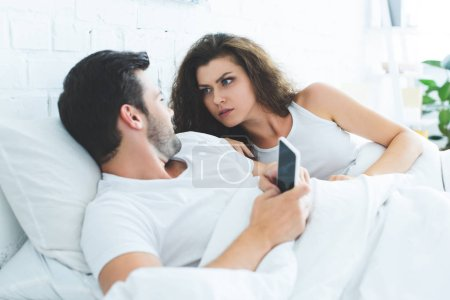 young couple looking at each other and quarreling about smartphone in bed, relationship difficulties concept