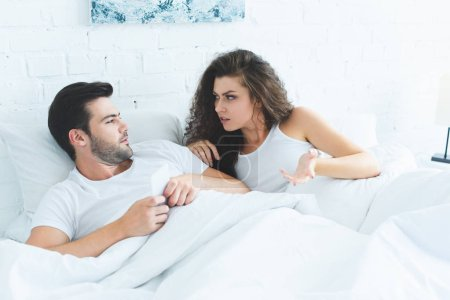 young woman quarreling with boyfriend using smartphone in bed, relationship difficulties concept